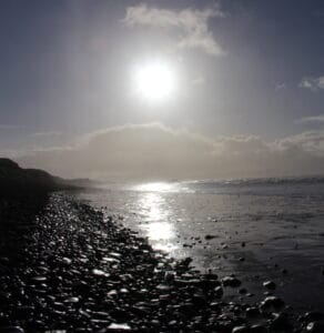 'Path' of sunlight on sea and pebble beach